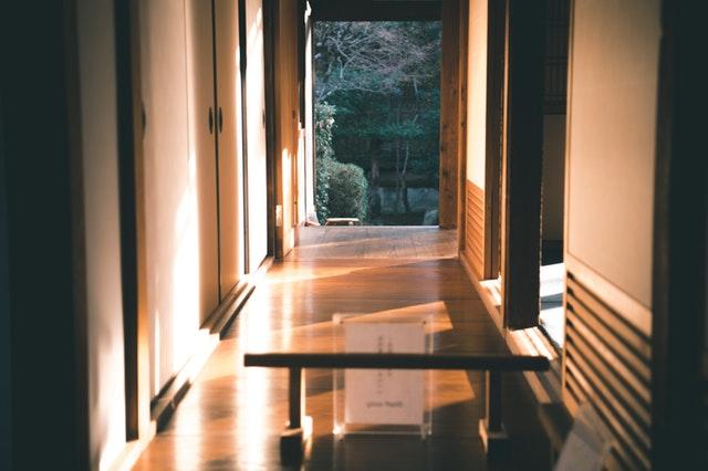 Pohľad cez sklenené dvere na úzku chodbu obloženú drevom vedúcu do záhrady