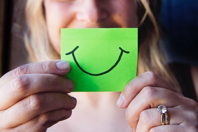 Žena drží pred tvárou zelený papierik s úsmevom.jpg