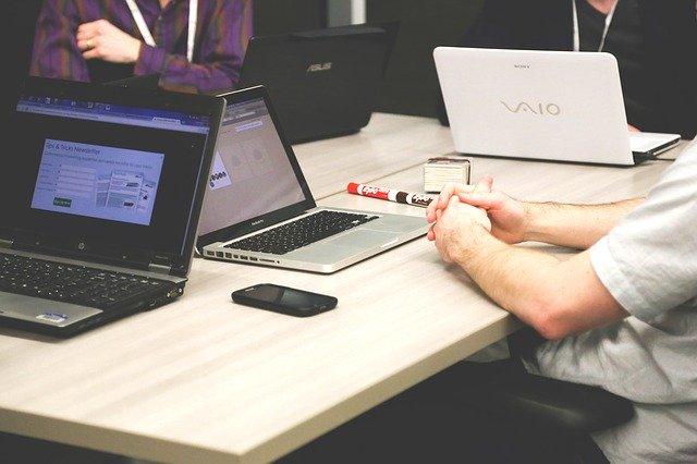Dvaja ľudia sedia oproti sebe za stolom pri počítačoch