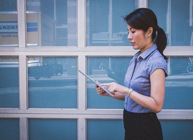 Žena stojí vedľa okien a pozerá do tabletu